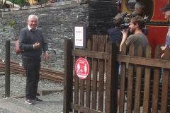 … so hands her handbag to Sir Gareth, who is too slow to hide it from a photographer (with suitable banter)!