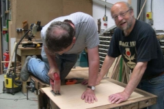 Neil and Charles cut out a shape in ply …
