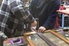 … before Graham lends Bill a hand, securing leather straps to the drop light windows …