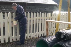 John makes use of the good weather to finish painting the fence to Maespoeth car park.