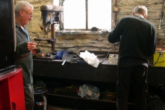 In the Engine Shed, Bob and Steve fettle up the remaining modified corner brackets for the waggon …