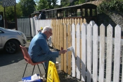 In Corris, The first train has arrived and Phil is already at it, painting the station fence …
