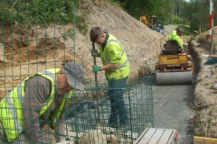 … before being passed to the baskets by machine, and placed by hand. Preparation for the next step up of gabions is in progress, rolling by machine but next to the end gabion, by hand punning.