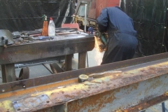 Adrian has set out the new gantry spreader beam (using the old one as a pattern) and drilled bolt holes as required, and is here shaping a gusset plate to fit ...