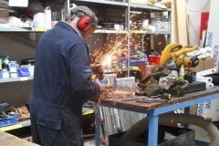 Thursday, 18.7.2019. Adrian gets the sparks flying, as he cuts components from pieces of scrap for carriage No. 23's handrails …