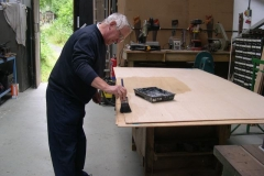 … while Graham treats ply with waterproofer …