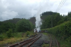 It is a wet day (the first really wet day after re-starting operations this year), so the steam really shows up well – with No. 7 emerging through it as it gets going up the bank south of Maespoeth.