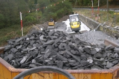 The rest of the geotextile is laid out, another layer of stone is rolled while more stone awaits placing.