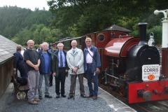 Author of Corris books Gwyn Briwnant Jones, poses with his travelling companions in front of loco No. 7 and train at Maespoeth.