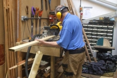 Elsewhere in the Carriage Shed, John is cutting timber …
