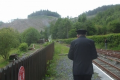Andrew (Controller) watches the train make its way up Maespoeth Bank, as his son films its progress from the other side of the tracks.