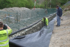 Gareth rolls out geotextile as Richard positions it in the trench, and Jack stops it sliding down too far!