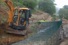 The geotextile is then folded back over the stone (to prevent pollution by soil) as the excavation at the end of the gabions is widened to take to solid ground – and in the distance, a lorry load of stone is delivered.
