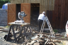 John has been cutting up firewood (between trains) while Peter stains the new woodwork on the fuel store.