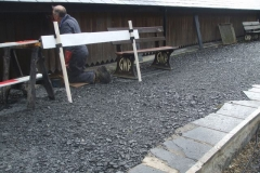 With all the firewood cut up, John sets to, finishing the re-staining of the west side of the Carriage Shed …