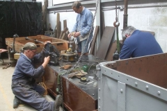 """Thursday, 24.6.2021. Adrian drills new holes in the floor of Heritage waggon No. 5, while Tony waterproofs the frames, and Nick welds """"bits"""" on the body …"""