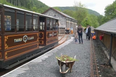 A small group of passengers receive their Shed Talk on the weeded South Platform while a waggon is hand propelled after depositing slate sub-base at the end of the North Platform.