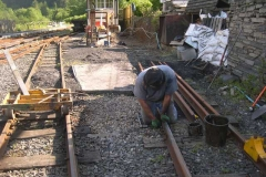 """Richard tightens fish bolts after laying """"new"""" rails on the ballast and fuelling siding …"""