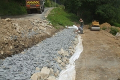… and rolling, so that the peeled back edge of the geotextile can be placed over the new stone …