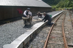Andrew Pugh is re-bedding displaced platform edging on the South Platform, under the close eye of Guard John Arnold.
