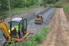 … after a load of blinding stone arrived from Aberllefenni Quarry, which has been spread and rolled to form the foundation and drainage layer under the first part of the future embankment.