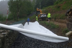 … and then it is all hands to roll out geotextile …
