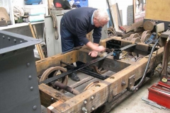 With the waggon frames turned over again and with tie bars completed and fitted by Chris and Bob, Graham gives the hidden ironwork a protective coat of bitumen paint