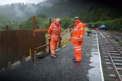 John and Dick are setting fence posts at the rear of the platform on a rather wet day …