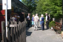 A group of passengers chat with staff before entering their train on a lovely, sunny afternoon.
