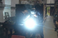 ... while in the Carriage Shed, Adrian welds while Bob looks on (trying out the welding hood).