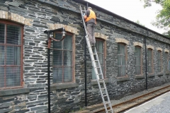 Meanwhile Peter has moved up in the world to improve the appearance of the engine shed drainpipes.