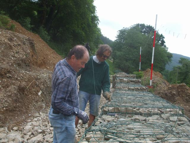 Friday, 12.6.2020. The rain forecast for the past two days has largely failed to materialise, so locally resident volunteers finish off levelling stone and stitching the lids down of the gabion baskets.